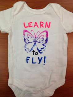 "Onesie decorated using a butterfly stamp with fabric paint gradient and fabric markers for lettering ""Learn to Fly!"""