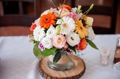 A colorful flower arrangement with a tone of orange is a perfect choice for a rustic wedding!