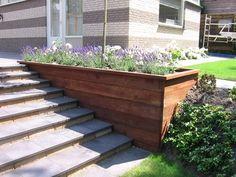 luie trap gemaakt van tegels met pilestoneblokken, daarnaast een plantenbak van hardhouten damwand in tuin in Bilthoven