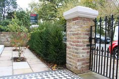 Brick pillar and black railings in contemporary London front garden.