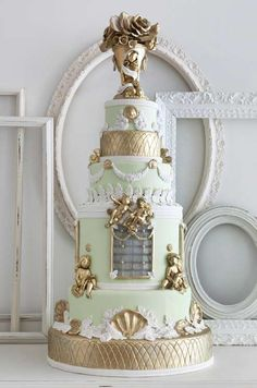 Gold and white sculptural elements pop against this light green wedding cake.