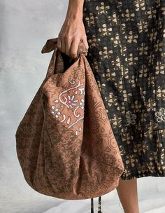 "Versatile Furoshiki bag is made from one seamed rectangle of cloth and tied at the shoulder. Functional and a great conversation piece. Hand embroidery adds to the interest. Width 32"".   Made by Sahara."