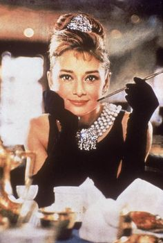 "Audrey Hepburn In ""Breakfast at Tiffany's"": Belgian-born actress Audrey Hepburn in a black, shoulderless dress, matching gloves, and a tiara, smiles with a cigarette holder in her hand, in her role as Holly Golightly the film, ""Breakfast at Tiffany's,"" directed by Blake Edwards, New York, New York, 1961. (Photo by Paramount Pictures/Courtesy of Getty Images)"