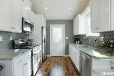 Kraft home #remodel and kitchen design. All new stainless steel appliances, stark white cabinets, grey and white #backsplash. Beautiful marbled counter tops.  #veronohomes realestate #staging #house http://www.verono.com/kraft/