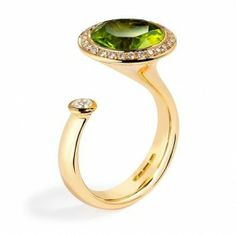 Satellite in peridot and diamond by Andrew Geoghegan. A fantastic dress ring set with a round cut peridot of 3.47ct and a round brilliant cut diamond of 0.10ct. The total weight of the diamonds surrounding the peridot is 0.15ct. Diamond quality G/vs.