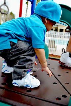 El chico lleva los zapatos blancos, los jeans gris, una camisa azul y una gorra azul.