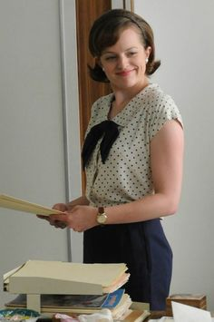 In the heat of summer, Peggy's blouse gets briefer—this one is a white bow blouse with navy polka dots and tie, worn over a navy skirt.