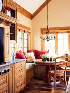 Such a cozy dining area! Love the wood cabinets, carved corbels and wainscoting on the bench, comfy pillows, and large windows around the banquette set.
