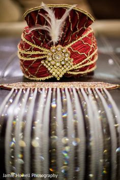 red safa (turban) with gold and diamonds and a sehra (the sort of beaded veil that attaches and hangs down over the face).