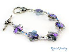 """Stacy"" This pretty 7 1/4 inch bracelet has 6 crystal cut reflective crosses (purple/grey AB),  $28  www.rejoicejewelry.com"