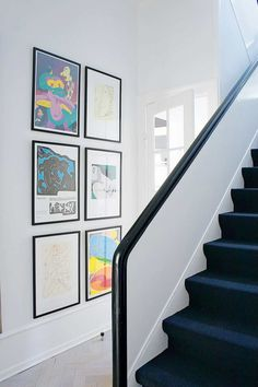 A black soft carpet on the stairs and the black-handed handrails gives the staircase to the first floor a distinctive expression that breaks with the otherwise bright room.