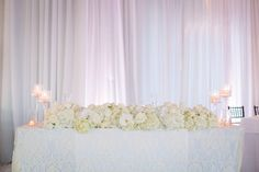 floral table runner, stemmed candle holders, all-white décor white drapery at…
