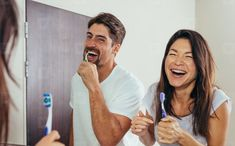 Smiling man and woman brushing teeth in bathroom. Couple brushing teeth in front of bathroom mirror and laughing. Smiling Man, Dental Floss, Photo Couple, Republic Of The Congo, Going To Work, Looking For Women, Laugh Out Loud, Teeth, Medical