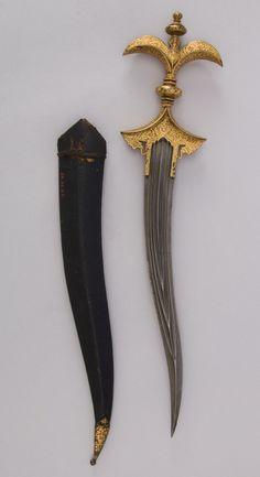 Chilanum Dagger with Sheath      Dated: 18th century     Culture: Indian     Medium: Iron, gold, leather     Measurements: H. with sheath 16 3/8 in. (41.6 cm); H. without sheath 15 1/4 in. (38.7 cm); H. of blade 10 13/16 in. (27.5 cm); W. 3 9/16 in. (9 cm); D. 1 in. (2.5 cm); Wt. 11.4 oz. (323.2 g); Wt. of sheath 1.3 oz. (36.9 g)