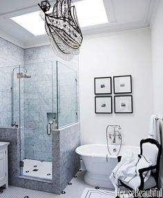 """The master bath's crystal ship chandelier """"was a whimsical last-minute selection."""" Floor tiles from Ann Sacks. Sunrise Specialty tub.   - HouseBeautiful.com"""
