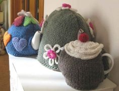 Trio of tea cosies! A small cherry cake tea cosy cup or personal teapot), medium rainbow hearts tea cosy cup teapot, this will fit the majority of standard teapots), and large loopy flowers tea cosy (big 8 cup teapot). Worked flat and seamed. Knitted Tea Cosies, Knitted Hats, Crochet Geek, Knit Or Crochet, Tea Cosy Pattern, Teapot Cover, Tea Cozy, Flower Tea, Mug Rugs