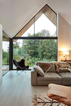 In this double height modern living room, large windows follow the roof line and provide ample natural light to the room.