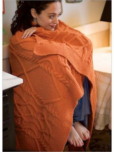 This designer scales her striking arrangement of cable crossings to the generous proportions of this cozy afghan. Ropelike strands weave in and out on a background of reverse stockinette stitch, and seed stitch forms a deep border around the edges. A c