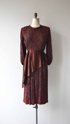 Vintage late 1930s, early 1940s rum raisin rayon crepe dress with sequin arabesques, shoulder pads, bishop cuff sleeves, fitted waist, asymmetrical silk satin peplum, sequin detailed skirt and metal side zipper. --- M E A S U R E M E N T S ---  fits like: small shoulder: 15 bust: 36 waist: 26 hip: 38 length: 45.5 brand/maker: n/a condition: excellent  ✩ layaway is available for this item  To ensure a good fit, please read the sizing guide: http://www.etsy.com/shop&#x2...