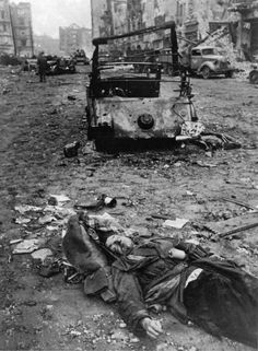 Desperate last stand: Volkssturm militia fighter lies dead in a devastated Berlin street. He still carries stick grenades and he is not wearing a uniform -- which, under normal circumstances, would have meant execution by firing squad, the fate reserved for all guerrillas.