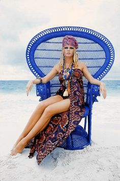 1968<> | Brigitte Bardot yields to the allure of a vividly painted peacock on a beach in the south of France.