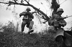 Members of the 3rd brigade, First Air Cavalry, jump into a ditch after Communist troops ambushed them as they moved down Highway One towards Hue