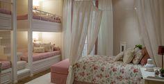 O quarto das filhas foi preparado com beliches para receber as frequentes visitas das amigas. As estampas florais, as cores delicadas e a cama com voil deixam o ambiente feminino e romântico.