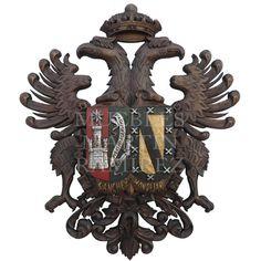 Águila Imperial Cadete con apellidos, talla artesanal en #madera #TallaMadera. Águila bicéfala de #Toledo, coronada, con un escudo con los motivos heráldicos que el cliente desee y el collar del Toisón de Oro. Realizado en madera de abedul, tratada con extracto de nogal, betún de Judea y cera virgen. Para darle un acabado brillante, se han utilizado las técnicas de patinado y bruñido. El escudo puede ir en el mismo color que el águila o puede ser policromado, como en la imagen.