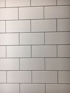We love the idea of having white metro tiles with grey grout, and near the bottom having a row of bright red (or maybe blue) tiles to introduce a splash of colour.  We think this would look good with the greys...