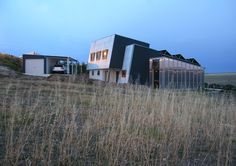 Aldinga Arts Eco Village sustainable house.  The building tilts to the north and is partially embedded in the upper slope of the site. The elements of earth mass, internal concrete walls and floors, north sun, ventilation and shading work together so efficiently that internal comfort in this house requires no additional heating or cooling. The semi-transparent conservatory on the eastern side transfers solar-warmed air into all internal spaces during winter.