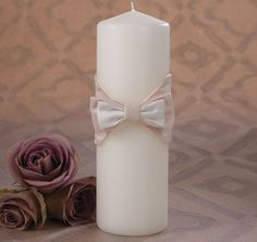 The Dignified Elegnace Unity Candle is adorned with a champagne/ivory or ivory/ivory sophisticated bowtie