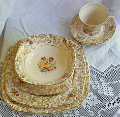 H & K Tunstall, England. Near complete 'Tapestry' dinner set. Pre-WWII. I Serving bowl with lid; 1 Serving platter; 1 Gravy boat; 6 Dinner plates; 6 Entree plates; 6 Bread and butter plates; 5 Tea/coffee cups; 6 saucers. One dinner plate is stained.