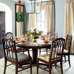 #RoundDiningTable - Place a round table in a square-shaped room for easier Christmas entertaining. The circular shape encourages conversation flow between all guests, so you're not stuck talking just to the people on either side of you. An oversize lantern casts a romantic glow and is a fresh alternative to a traditional chandelier.