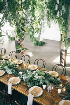Woodsy Table Setting: Play up the outdoorsy element with a fern garland runner *and* a hanging fern display. The bountiful foliage will transport guests into a woodsy wonderland — not to mention, it'll make for some seriously stunning pictures. (via Hikari Photography / The Style Co)