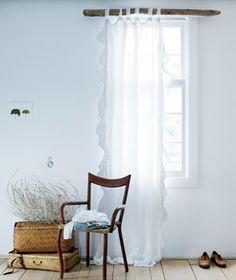 I love the idea of using driftwood as a curtain rod. Beach inspired decor :)
