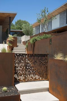 The motif is expressed in weathered steel for a gate. #stairs #outdoor #walkway