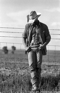 sexy cowboy leaning on a wire fence on a ranch in New Mexico