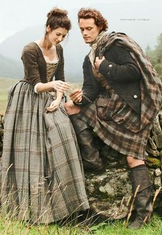 Claire and Jaime in the beautiful Scottish Highlands. Claire is wearing a brown dress with neckline edged in white lace and criss-cross laced floral stomacher. | Outlander on Starz | Costume Designer TERRY DRESBACH