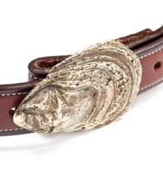 """SID MASHBURN OYSTER SHELL BUCKLE BRASS $75 Handcast from an oyster that a Massachusetts metalworker plucked from a bed behind his workshop. Made to fit a 1"""" strap with snaps and holes. Absolutely one of our favorite things. brass 2.75"""" width/1.75"""" height fits a 1"""" strap USA polish and shineSold at Sid Mashburn"""