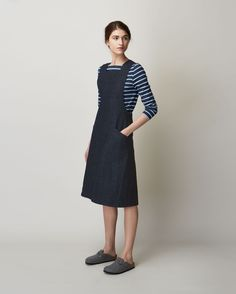 Pinafore front dress in deep, indigo-dyed denim. Slanted patch pockets. Wide straps, crossing over at back. Large, asymmetric pleat at back. Concealed side zip.