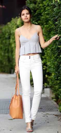 Adriana Gastelum is wearing a grey pleated crop top from Zara, high waisted white jeans from Salsa, bag from Mansur Gavriel, mules from Guess and sunglasses from Quay