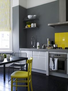 Our kitchen has a yellow tile countertop and backsplash. We're trying to work with it for now. We're loving the grey and yellow here.