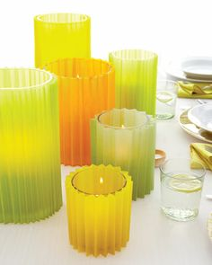 pleated vellum hurricane shades  - Make 1/4-inch, 3/8-inch, or 1/2-inch scores the accordion fold and attach ends with double sided tape around your candle holders.  Could use patterned paper as well as vellum.