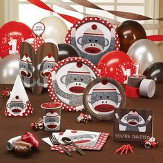 Sock Monkey Red 1st Birthday Deluxe Party Pack for 16  Includes (16) invitations, dinner plates, dessert plates, cups, forks, spoons, (40) napkins, solid-color tablecover, centerpiece, foil balloon, (18) balloons (3 colors), curling ribbon (3 colors), crepe paper rolls (3 colors), (16) cone hats, #1 candle and cake candles.