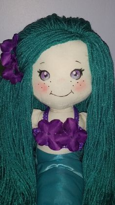This is an 18 mermaid rag doll made with long Aqua Yarn hair and purple eyes.  Aquamarine comes with a purple halter top that is removable and a
