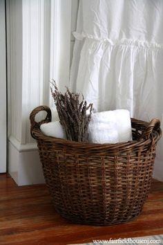 Vintage wicker basket backed by crispest white towels...lovely in a guest bathroom
