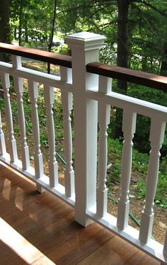 Railing designed with double dark and light top rails. This allows for the rail to appear visually lower yet meets the building code requirements for height and safety. Squash blocks, post, cap, and balasters all add beauty to the porch design while securing the railing firmly to the porch structure.