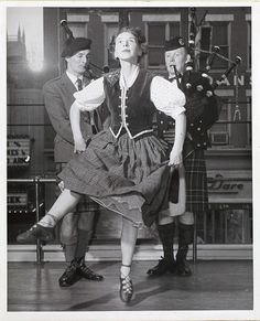 Mrs. MacLachlan performing a Highland dance, while her husband Duncan MacLachlan (left), and James Nowlan (right), play bagpipes.