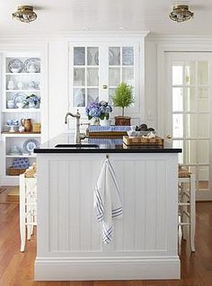 Kitchen with cottage appeal! I love the bead board and the divided glass doors.