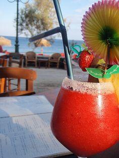 Strawberry Daiquiri by the beach in Santorini, Greece.